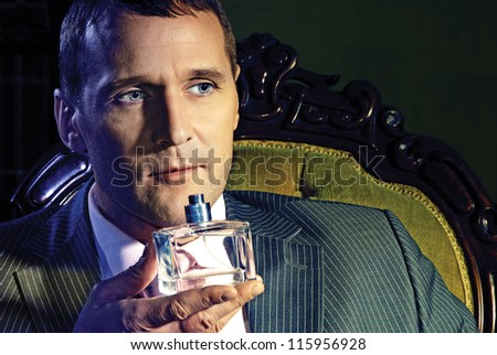 Portrait of a mature man, tasting parfume - stock photo
