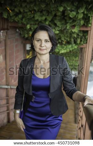 Portrait of a mature sad woman in a blue evening dress.  - stock photo