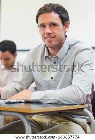 Portrait of a mature student taking notes in lecture in college - stock photo