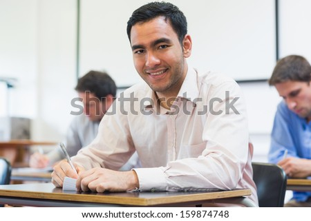 Portrait of a mature student taking notes with others in lecture in college - stock photo