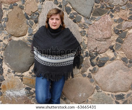 Portrait of a mature woman near a stone wall in the background - stock photo
