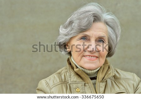 Portrait of a mature woman near wall on street