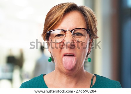 portrait of a mature woman showing her tongue - stock photo