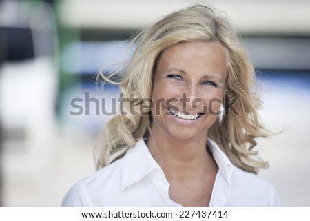 Portrait Of A Mature woman smiling at the camera in front of the office. She is confident with a lot of leadership. - stock photo