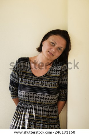 Portrait of a mature woman standing against the wall - stock photo