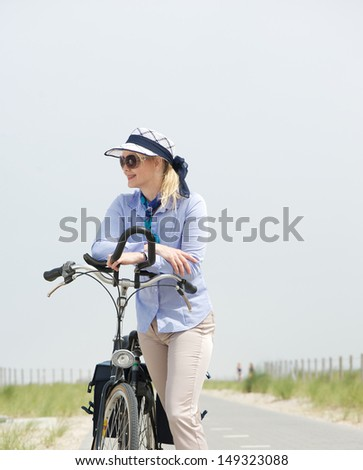 Portrait of a mature woman standing with bike on street - stock photo