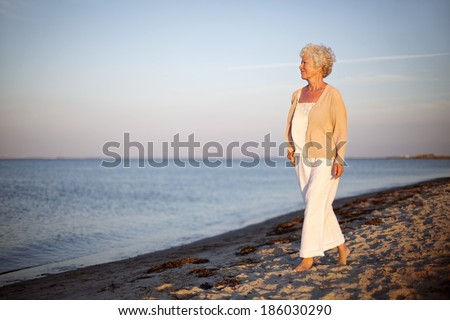 Portrait of a mature woman walking on the beach looking at the sea. Relaxed old lady strolling on the beach with lots of copyspace. - stock photo