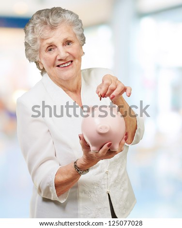 Portrait Of A Mature Woman With A Piggy Bank, Indoor - stock photo