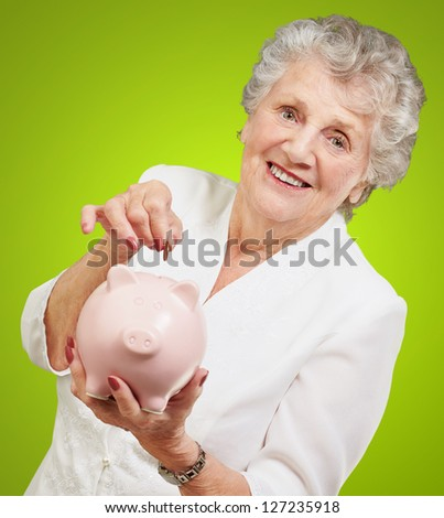 Portrait Of A Mature Woman With A Piggy Bank On Green Background - stock photo