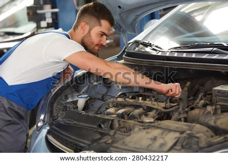 Portrait of a mechanic about to repair a car's engine at his workshop