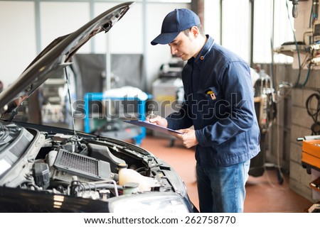 Portrait of a mechanic at work in his garage - stock photo
