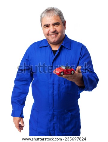 portrait of a mechanic holding a red car toy - stock photo