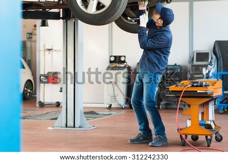 Portrait of a mechanic repairing a car in his garage - stock photo