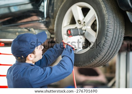 Portrait of a mechanic replacing a wheel - stock photo