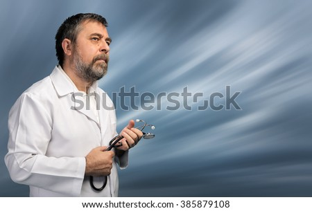 Portrait of a medical doctor with stethoscope posing against blurred sky with copyspace