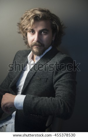 Portrait of a men with beard and mustache in studio gray background - stock photo