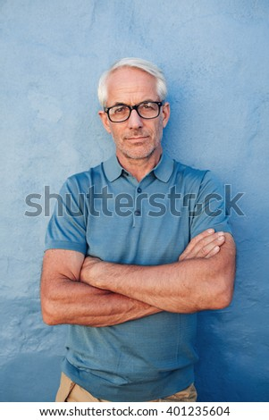 Portrait of a mid adult caucasian man standing with his arms crossed against a blue background. Caucasian male wearing glasses staring at camera. - stock photo