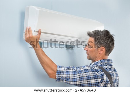 Portrait Of A Mid-adult Male Technician Fixing Air Conditioner On Wall - stock photo