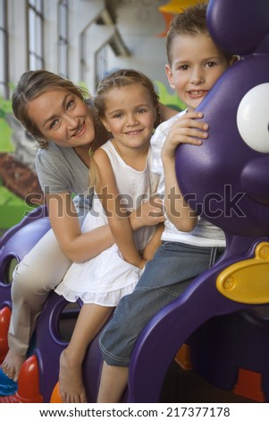 Portrait of a mid adult woman with two children sitting in a caterpillar train - stock photo