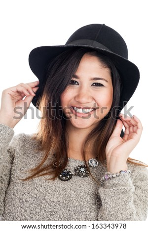 Portrait of a mid 20s Asian woman wearing a hat isolated on a white background - stock photo