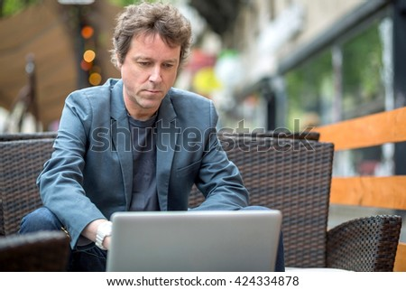 Portrait of a middle age businessman siting on the terrace of a coffee shop and speaking on the phone. - stock photo