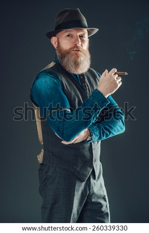 Portrait of a Middle Age Man with Goatee Wearing Fashionable Wear Holding a Cigarette with One Arm Crossing Over his Stomach While Looking at the Camera. Isolated on a Gray Background. - stock photo