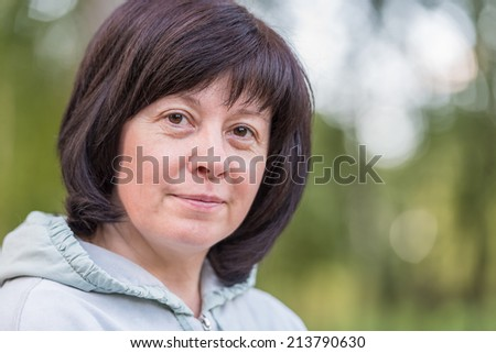 portrait of a middle-aged brunette woman on a background of nature - stock photo