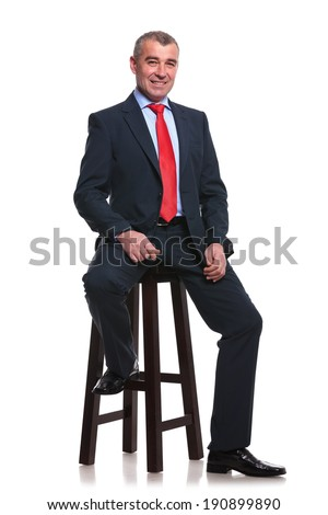 portrait of a middle aged business man sitting on a high stool and smiling for the camera. isolated on a white background - stock photo