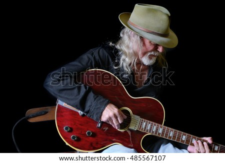 Portrait of a middle aged Caucasian man with long hair and a white beard wearing  a fedora hat and a black shirt while playing an electric guitar. Black background and sidelighting.