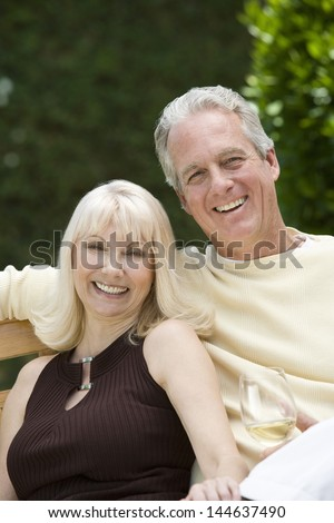 Portrait of a middle aged couple with wineglass in the garden - stock photo