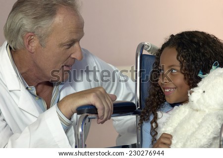 Portrait of a middle aged doctor talking to a young girl in a wheelchair - stock photo