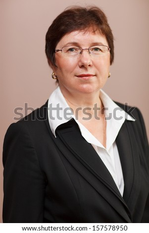 Portrait of a middle-aged experienced dedicated female business executive or manageress wearing glasses and a smart jacket