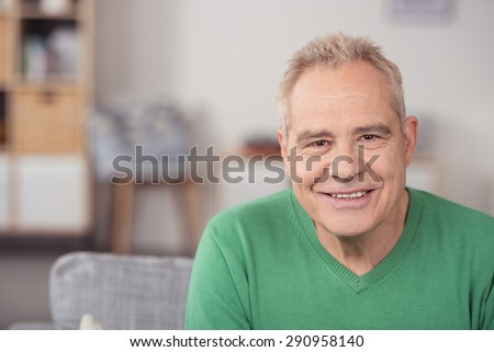 Portrait of a Middle Aged Man in Green Casual Shirt, Sitting at the Living Room While Smiling at the Camera. - stock photo