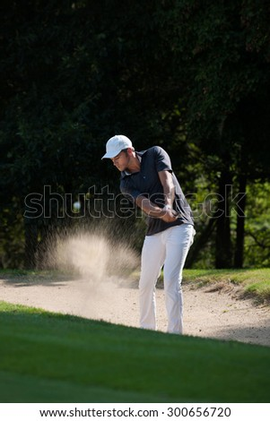 Portrait of a middle aged man trying to shoot his ball out of the bunker. He is playing golf with a white cap and the sand is flying around him