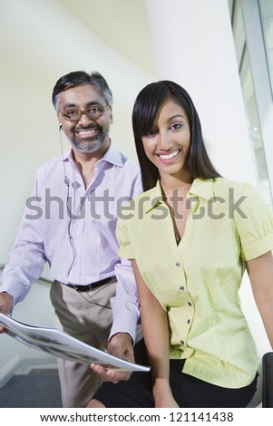 Portrait of a middle aged real estate agent showing building models to female coworker at office