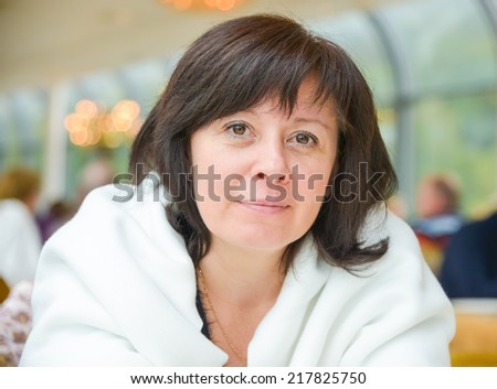 portrait of a middle-aged woman dark hair brown eyes is sitting in the apartment - stock photo