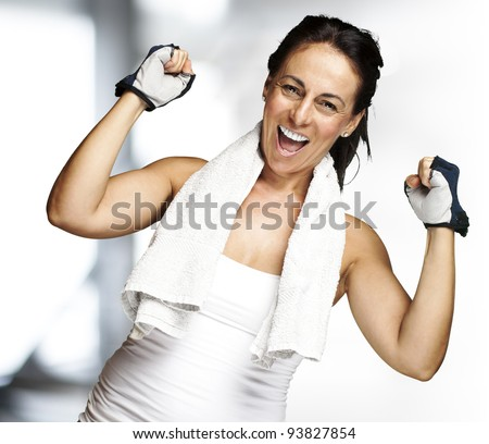 portrait of a middle aged woman gesturing a win symbol indoor - stock photo