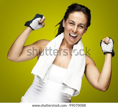 portrait of a middle aged woman gesturing win symbol over yellow
