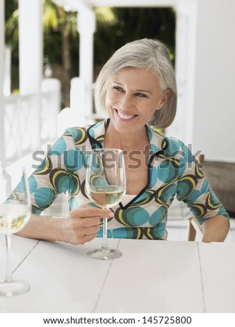 Portrait of a middle aged woman holding glass of wine at verandah table - stock photo
