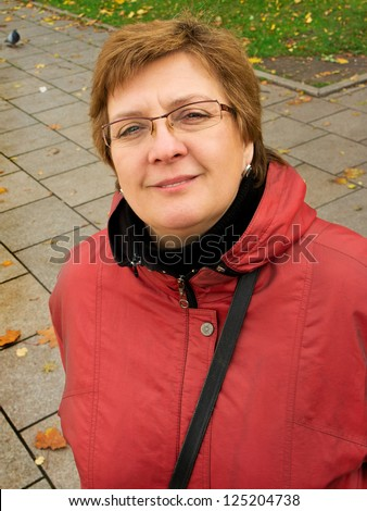 Portrait of a middle-aged woman in a red jacket - stock photo