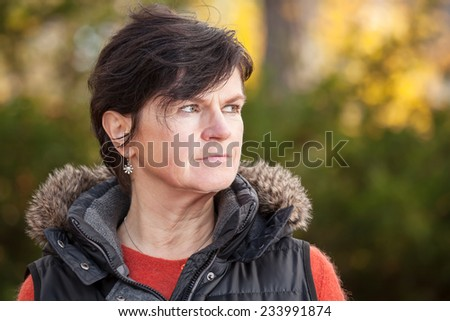 Portrait of a middle aged woman in autumn - stock photo