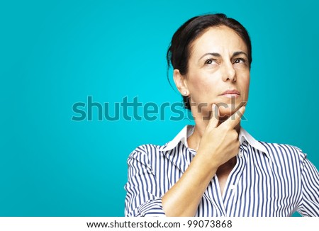 portrait of a middle aged woman thinking against a blue background - stock photo