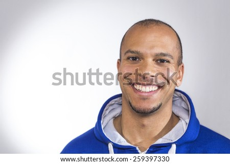 Portrait of a mixed race man smiling to camera in a blue hooded sweater - stock photo
