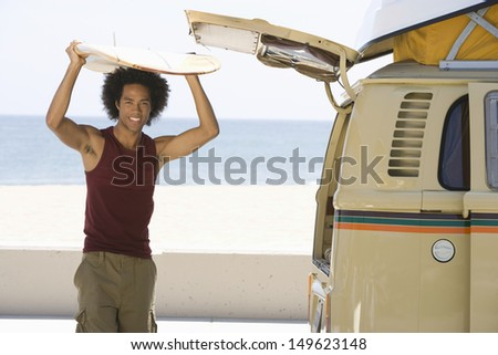 Portrait of a mixed race man with surfboard on head by camper van - stock photo