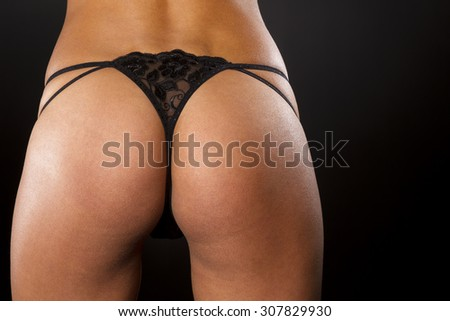 Portrait of a model with a black thong in a studio environment - stock photo