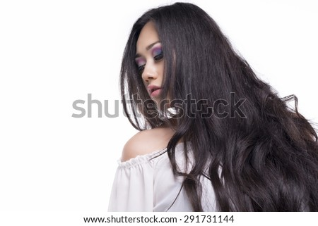 Portrait of a model with long and black hair isolated over white background