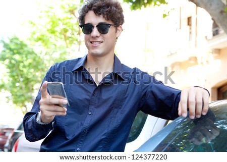 Portrait of a modern businessman leaning on a car using a smart phone and wearing shades outdoors.