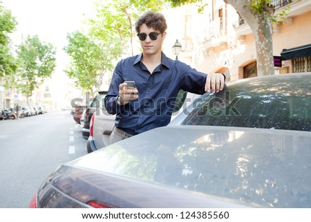 Portrait of a modern businessman leaning on a car using a smart phone and wearing shades outdoors. - stock photo