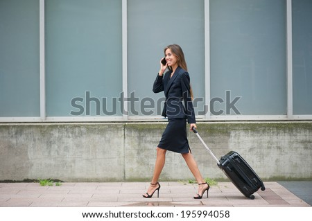 Portrait of a modern businesswoman traveling with suitcase  - stock photo