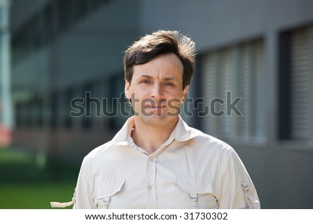 Portrait of a modern man with a building on the background - stock photo